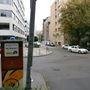 A képen az első kerülethez tartozó parkolóautomata látható, a háttérben az NM Zrt. székháza, a távolban lévő fehér autó mögött pedig egy másik zóna parkolóórája