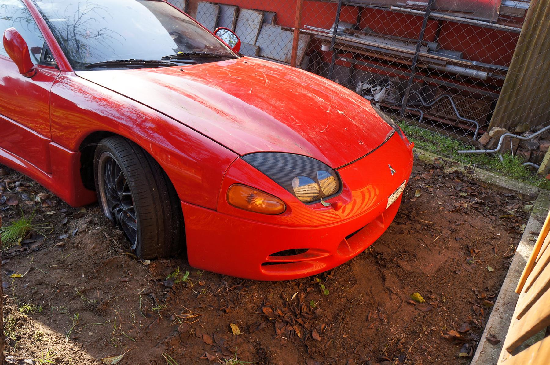 Egy másik, szerelés alatt álló autó, egy Maserati áll kint a műhely udvarán. Hátsó oldalablaka hiányzik, az utastérben bedobált alkatrészek láthatók. Ezt a fotót Márk készítette, amikor elment megnézni saját autóját Lászlóhoz