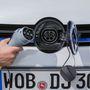 A kékes hátterű Volkswagen embléma-ajtó mögött találjuk a töltőcsatlakozót. A kábelt reteszelés védi a lopástól. A kábel hossza néhány méter csupán, hagyományos hosszabbítóval nem használható